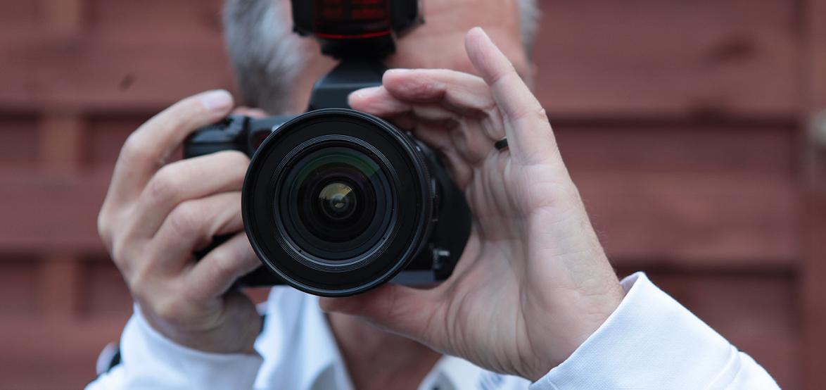 Uwe G. Bachmann hält eine Spiegelreflexkamera vor dem Gesicht.