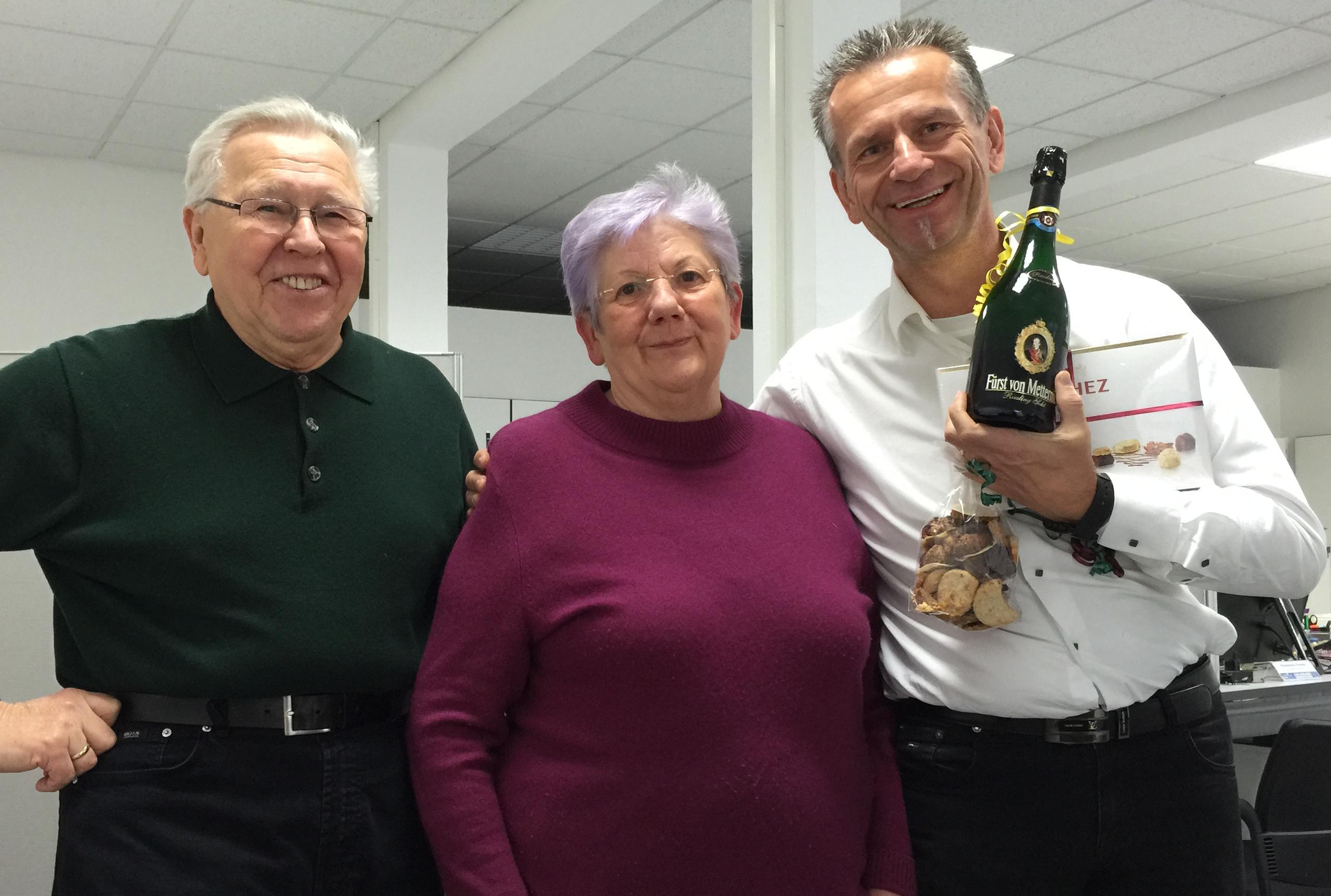 Uwe G. Bachmann und Frau und Herr Scholz stehen zusammen mit der überreichten Sektflasche im Büro Mahlsdorf.