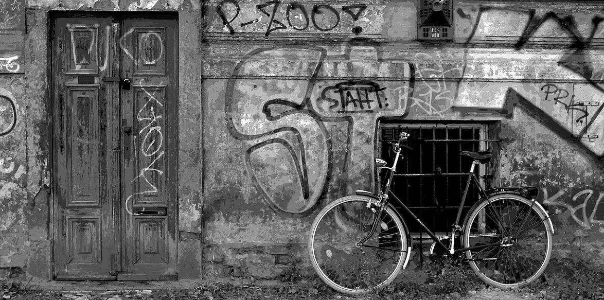 Ein Schwarz/Weiß-Foto auf dem eine Hauswand mit Tür abgebildet ist, an der Wand lehnt ein Fahrrad.